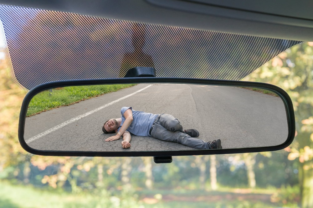 rear view mirror showing injured person from hit and run